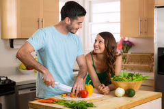 Handsome chef man and beautiful woman on a date chopping vegetables and a nutritious meal and salad stock photo