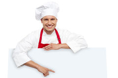 Handsome chef pointing at white billboard Royalty Free Stock Photography