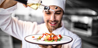 Handsome chef pouring olive oil on meal. In a commercial kitchen Royalty Free Stock Photography