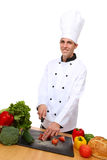 Handsome Chef Preparing Meal. A handsome man chef in the kitchen preparing food royalty free stock photos