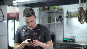 Handsome chef sending a text message in commercial kitchen stock footage