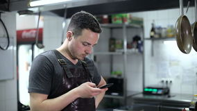 Handsome chef sending a text message in commercial kitchen stock video footage