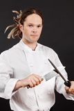 Handsome chef sharpening his knife Royalty Free Stock Image