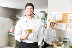 Handsome Chef Showing Cooking Skills In Kitchen. Portrait of young smiling cook holding food plate in kitchen stock photos