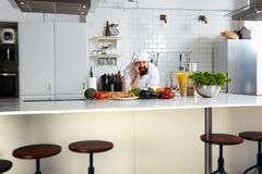 Handsome chef  in uniform standing on the kitchen Stock Photography