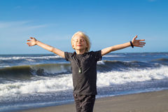 Handsome child with arms outstretched freedom concept. Handsome child at beach, arms outstretched in freedom concept Stock Photo