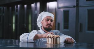 A handsome chubby man with chefs attire and a long beard, picks at this birthday cake with his finger and looks happy. When indulging in it. 4k stock video