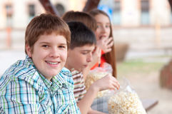 Handsome chubby teenager with his friends. Handsome chubby teenager spending time with his friends outdoor royalty free stock images