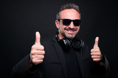 Handsome classy male listening good music. And showing thumbs up on dark background stock photography