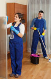 Handsome cleaners cleaning in room Royalty Free Stock Photography