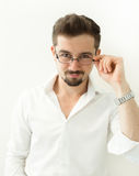 Handsome clever man holding glasses stand against white background. Leaning man in glasses and white shirt, portrait. Close up Smi Royalty Free Stock Image