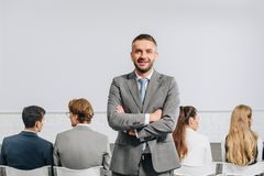 Handsome coach with crossed arms looking at camera during business training. In hub royalty free stock photography