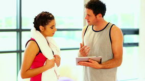 Handsome coach talking to sporty woman