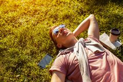 Handsome college man chilling in spring campus park. Happy guy student lying on grass with his phone and coffee beside. Handsome college man chilling in spring Royalty Free Stock Photo