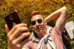 Handsome college man chilling in spring campus park. Happy guy student lying on grass and takes selfie. Using smartphone at sunset Stock Photos