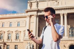 Handsome college man hanging in smartphone in campus park. Happy guy student walking by university. In summer Royalty Free Stock Photo