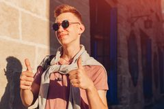 Handsome college man walking on city street. Happy guy student with backpack showing thumb up. Life is great Royalty Free Stock Image