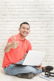 Handsome college student with his laptop giving thumbs up. Portrait of handsome college student with his laptop giving thumbs up Royalty Free Stock Image