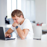 Handsome college student with laptop computer. In university library/study room Stock Photo
