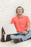 Handsome college student listening music on laptop while sitting. Portrait of handsome college student listening music on laptop while sitting on the floor Royalty Free Stock Photos