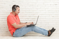 Handsome college student playing game on laptop while sitting on Stock Images