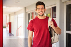Handsome college student. Portrait of a Hispanic college student carrying a backpack and standing in a school hallway
