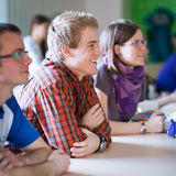 Handsome college student sitting in a classroom full of students Royalty Free Stock Image