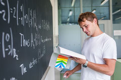 Handsome college student solving a math problem. During math class in front of the blackboard/chalkboard (color toned image Royalty Free Stock Photos