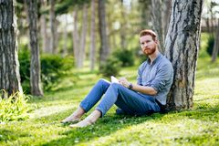 College student studying in park. Handsome college student studying in park Stock Photo