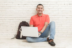 Handsome college student studying using laptop while sitting on Stock Photography
