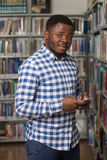 Handsome College Student Using Mobile Phone In Library. African Male Student Using The Phone In Library - Shallow Depth Of Field Royalty Free Stock Image