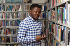 Handsome College Student Using Mobile Phone In Library. African Male Student Using The Phone In Library - Shallow Depth Of Field Stock Image