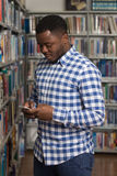 Handsome College Student Using Mobile Phone In Library. African Male Student Using The Phone In Library - Shallow Depth Of Field Stock Images