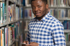 Handsome College Student Using Mobile Phone In Library. African Male Student Using The Phone In Library - Shallow Depth Of Field Royalty Free Stock Photo