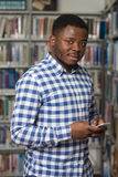 Handsome College Student Using Mobile Phone In Library. African Male Student Using The Phone In Library - Shallow Depth Of Field Stock Photos