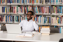 Handsome College Student Using Mobile Phone In Library. African Male Student Talking On The Phone In Library - Shallow Depth Of Field Royalty Free Stock Photography
