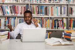 Handsome College Student Using Mobile Phone In Library. African Male Student Talking On The Phone In Library - Shallow Depth Of Field Stock Photography