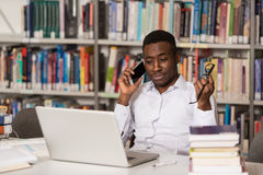 Handsome College Student Using Mobile Phone In Library. African Male Student Talking On The Phone In Library - Shallow Depth Of Field Stock Images