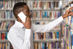 Handsome College Student Using Mobile Phone In Library. African Male Student Talking On The Phone In Library - Shallow Depth Of Field Royalty Free Stock Photo