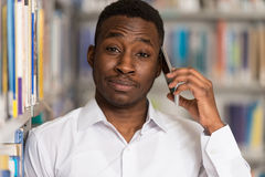 Handsome College Student Using Mobile Phone In Library. African Male Student Talking On The Phone In Library - Shallow Depth Of Field Stock Photos