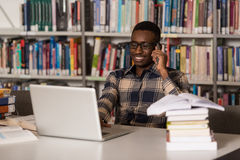Handsome College Student Using Mobile Phone In Library. African Male Student Talking On The Phone In Library - Shallow Depth Of Field Royalty Free Stock Photos