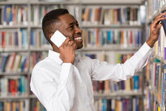 Handsome College Student Using Mobile Phone In Library. African Male Student Talking On The Phone In Library - Shallow Depth Of Field Royalty Free Stock Images
