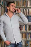 Handsome College Student Using Mobile Phone In Library. Male Student Talking On The Phone In Library - Shallow Depth Of Field Royalty Free Stock Photography