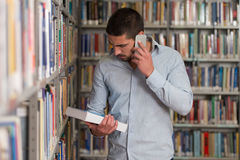 Handsome College Student Using Mobile Phone In Library. Male Student Talking On The Phone In Library - Shallow Depth Of Field Royalty Free Stock Photos