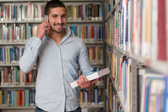 Handsome College Student Using Mobile Phone In Library. Male Student Talking On The Phone In Library - Shallow Depth Of Field Stock Photo