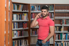 Handsome College Student Using Mobile Phone In Library. Male Student Talking On The Phone In Library - Shallow Depth Of Field Royalty Free Stock Images