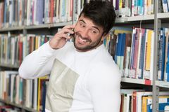 Handsome College Student Using Mobile Phone In Library. Young Bearded Student Talking Phone While Preparing for Exams in Univercity Library Royalty Free Stock Images