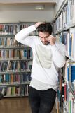 Handsome College Student Using Mobile Phone In Library. Young Bearded Student Talking Phone While Preparing for Exams in Univercity Library Royalty Free Stock Photography