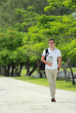 Handsome college student walking by at college park with backpac. Portrait of handsome college student walking by at college park with backpack and holding a Royalty Free Stock Photo