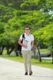 Handsome college student walking by at college park with backpac. Portrait of handsome college student walking by at college park with backpack and holding a Royalty Free Stock Photos